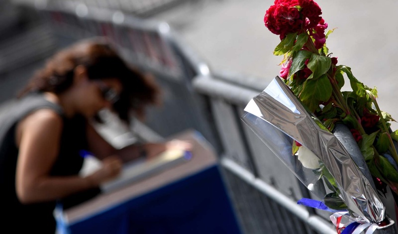 A woman signs the book of condolences in front of the French embassy in Rome on July 15, 2016, after the deadly attacks in Nice. (AFP PHOTO / TIZIANA FABI)